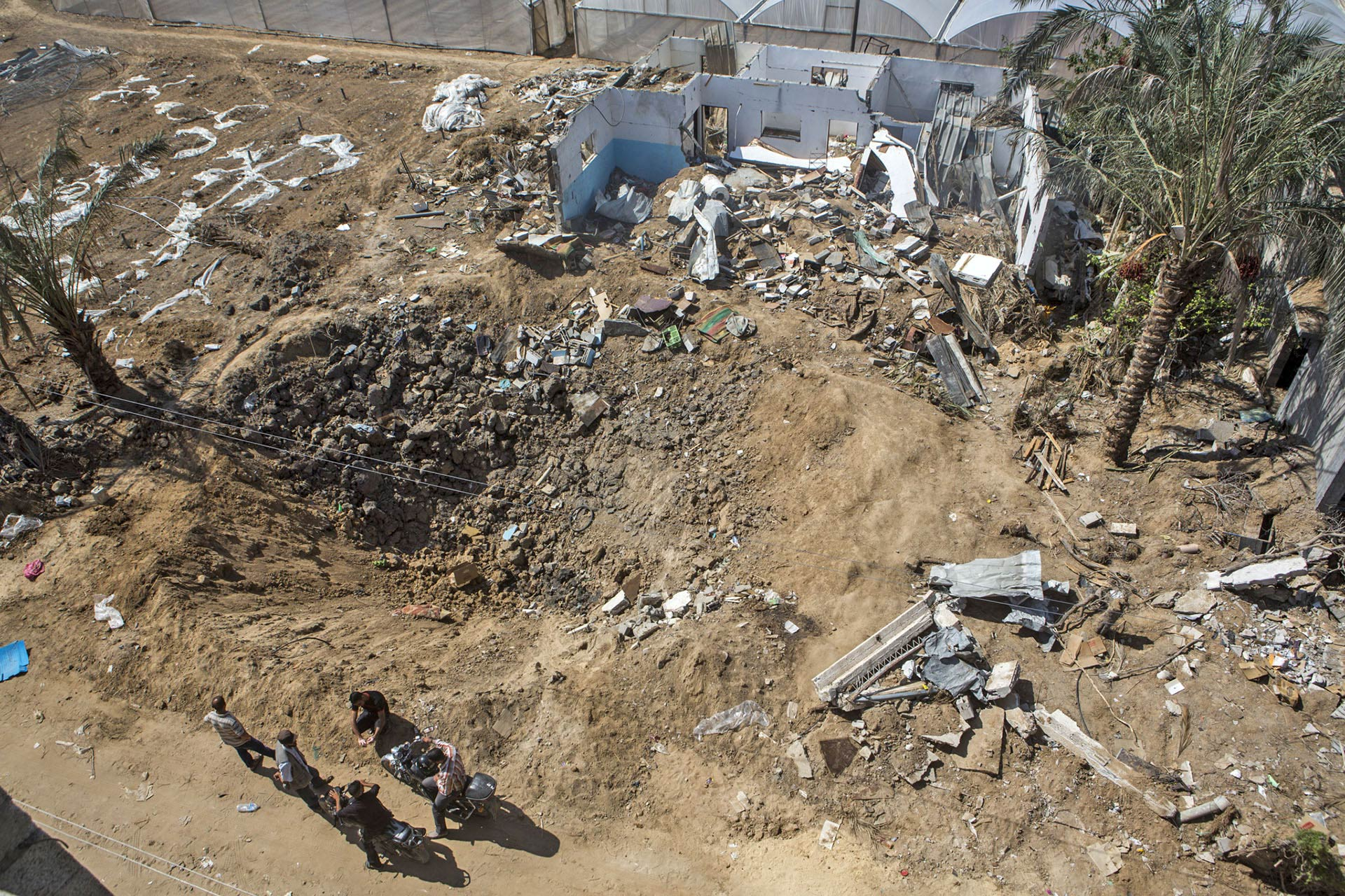 Seven trucks of sand were not enough to fill the bombed-out crater where Rafat's house once stood.