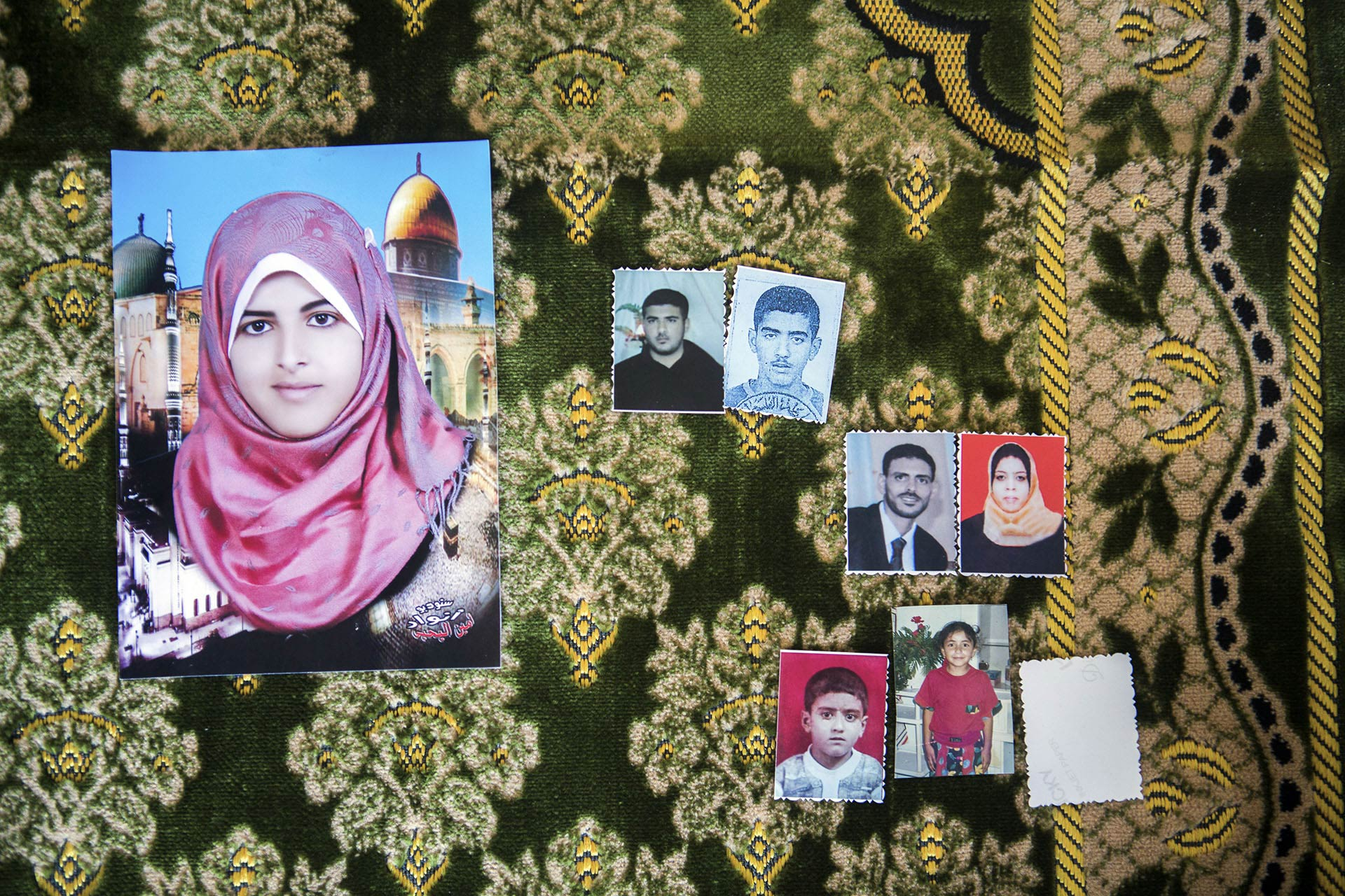 Photos of seven of the eight members of the al-Louh family that were killed, displayed on Iman al-Louh's prayer rug. Iman was using that rug when she was hit by a piece of concrete that flew into the room through a window.