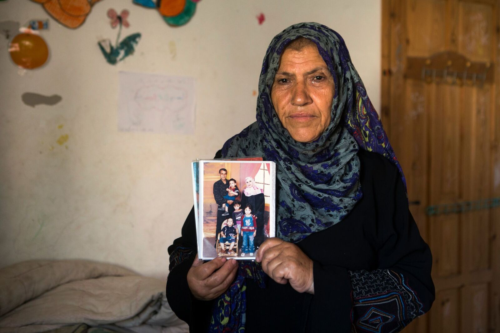 Khadija, Ibrahim's sister, holds photo of her brother and his family.