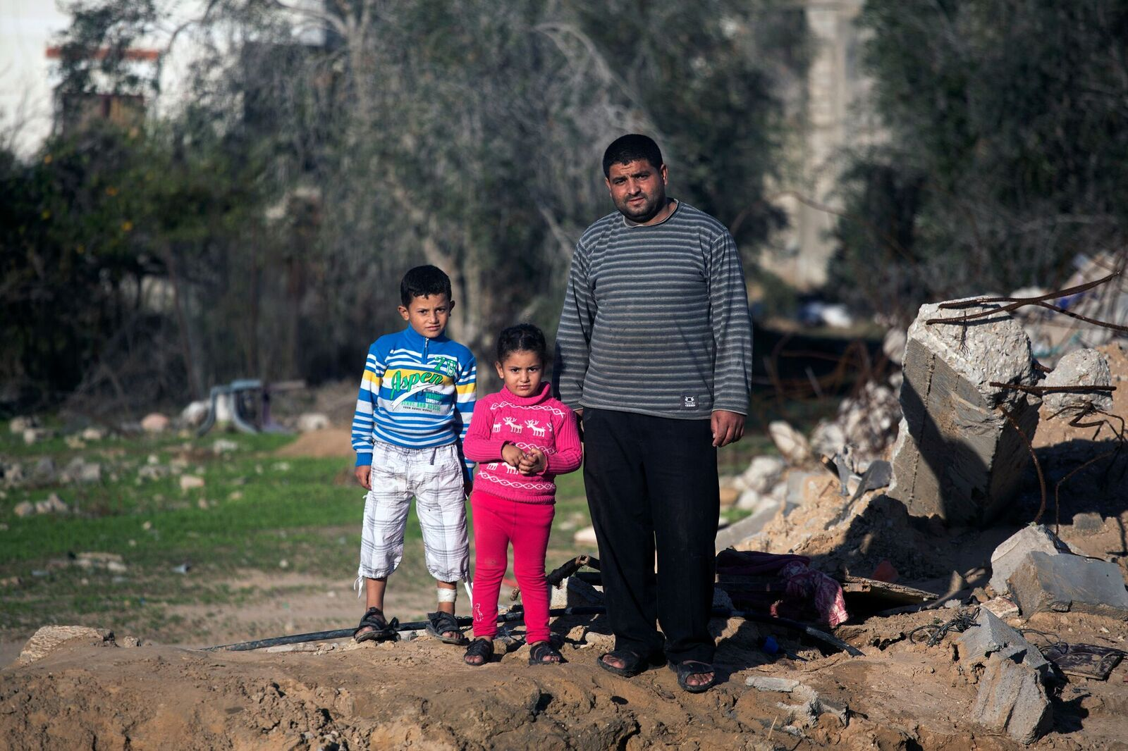 Hussein, one of the only three people to survive bombing of his family home, with his two children Husam and Olfat.