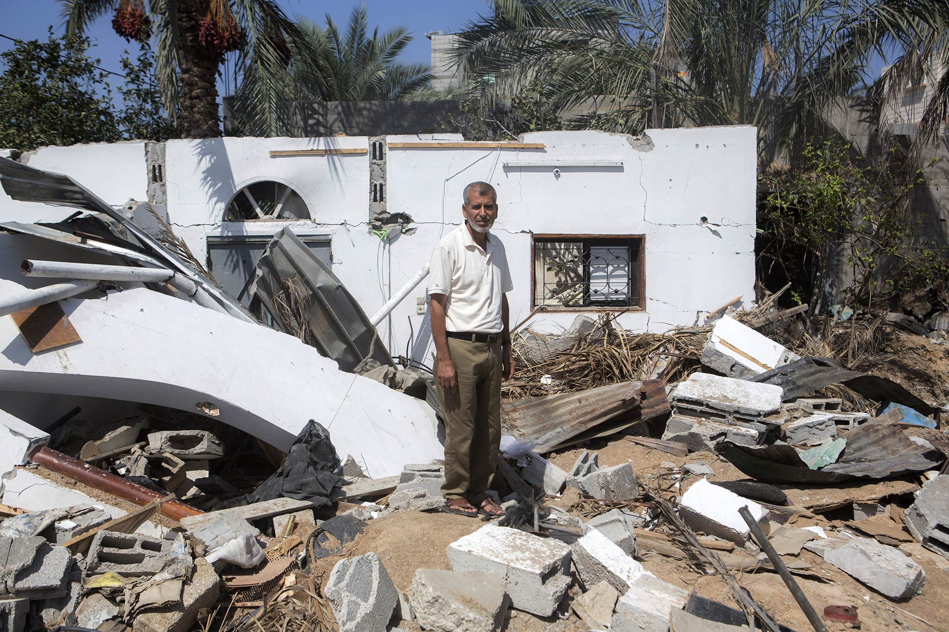 Mustafa in the ruins of his family's bombed homes.