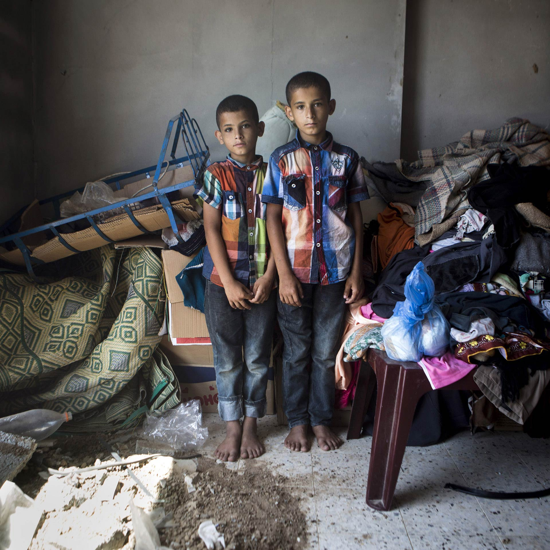 Ibrahim, the smaller of the twin brothers on the photo, says he misses his best friend, eight-year-old Maysara al-Louh. The two boys, Ibrahim and Abdallah, are standing in their destroyed bedroom, in Deir al-Balah, right in front of where the al-Louh family home used to stand. Their bedroom was damaged in the bombing that killed Maysara and seven other members of al-Louh family.
