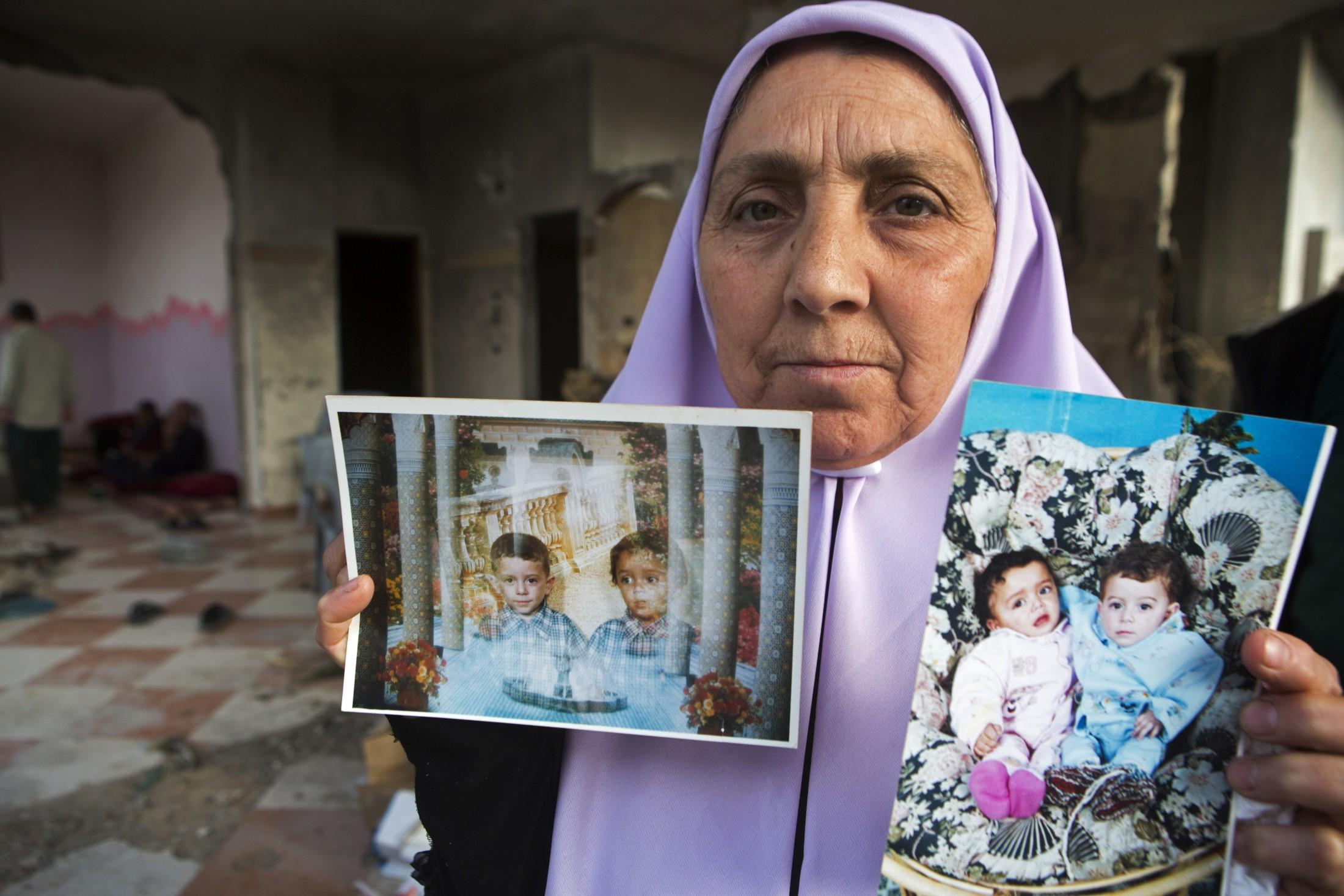 'Atef montrant les photos de son fils Talal et de son frère jumeau, Abdallah, tué lors de l'attaque.
